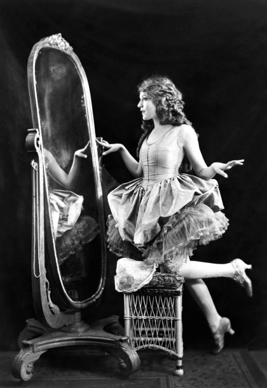 Actrice en latere auteur/filmproducente Mary Pickford werpt een blik in de spiegel. Credits: Alfred Cheney Johnston, 1920.