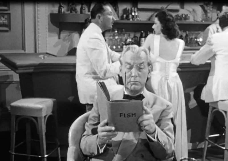 Emmett Vogan als Professor Martin die een boek leest in de film Dangerous Money uit 1946