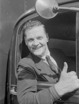 Een vrachtwagenbestuurder steekt zijn duim op. Ergens in Groot-Brittannië, 1940.