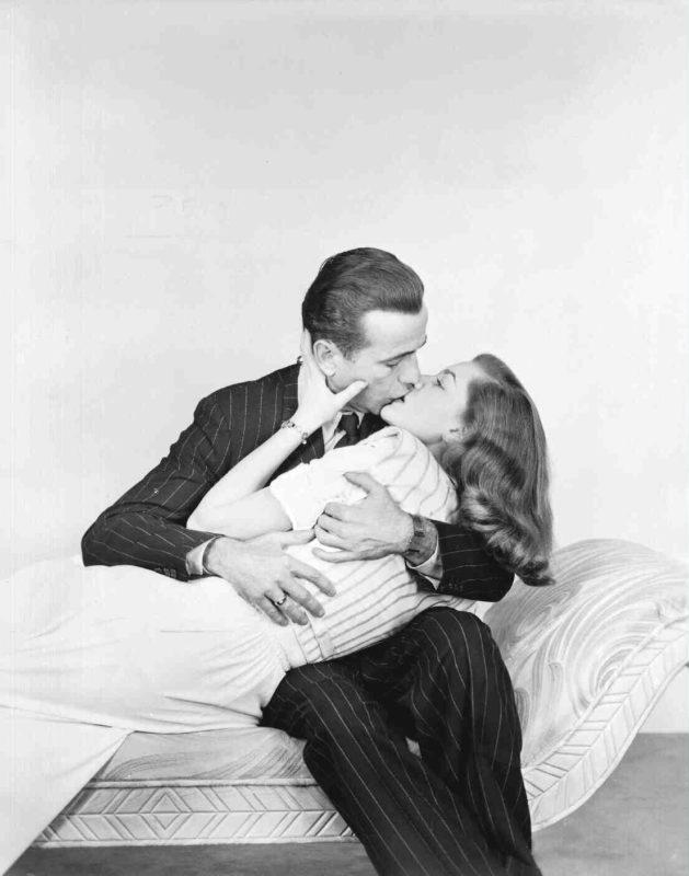 Humphrey Bogart kust zijn geliefde Lauren Bacall, een publiciteitsfoto voor film The Big Sleep. Credits: Warner Bros.