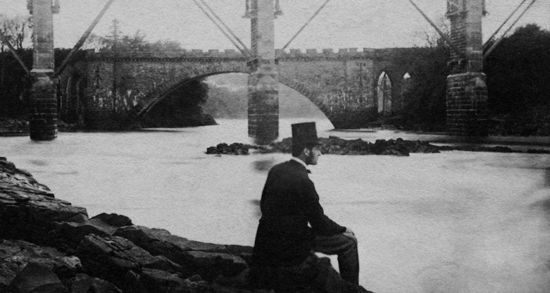 Een man alleen, zittende langs een rivier.